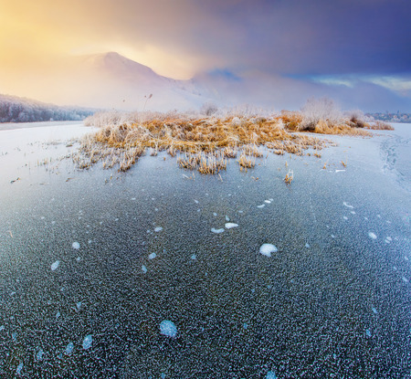 Sunrise on the frozen lake in the winter mountains photo