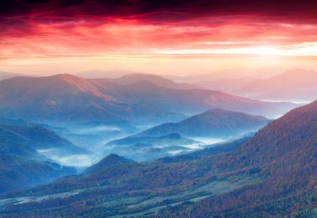 dramatic sunrise: Panorama of the autumn mountains. Foggy mogning. Stock Photo