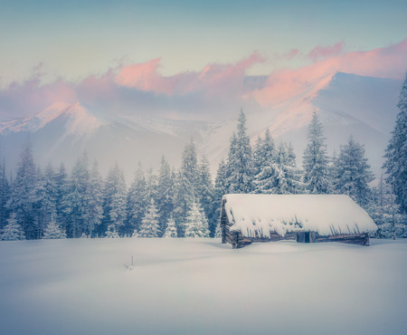 Foggy winter sunrise in mountains. Old ranch after huge snowfall. Retro style. Zdjęcie Seryjne