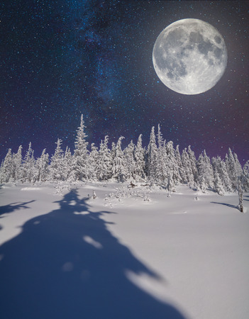 blue stars: Full moon in night sky in the winter mountains Stock Photo