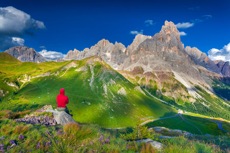 Climber admiring of the landscape of Pale di San Martino, Trentino - Dolomites, Italy. Cimon della Pala mountain ridge.