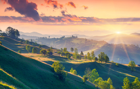 hill: Colorful summer sunrise in the Carpathian mountains with rolling hills and valleys in golden morning light Stock Photo