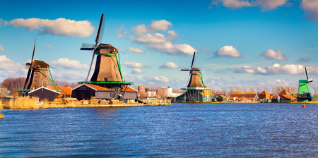 Authentic Zaandam mills on the water channel in Zaanstad willage. Zaanse Schans Windmills and famous Netherlands canals.