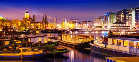 アムステルダムの美しい穏やかな夜景水と運河のボートで反射と建物の夜時間イルミネーション。