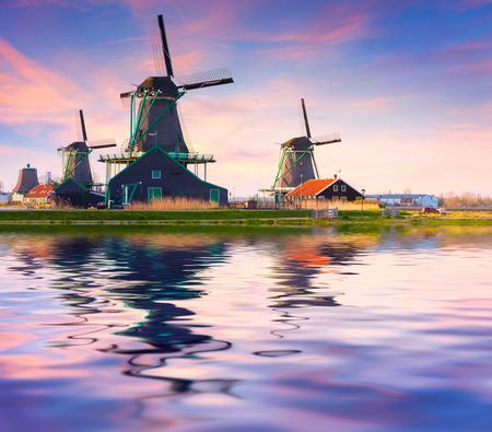 zaandam: Authentic Zaandam mills on the water channel in Zaanstad willage. Zaanse Schans Windmills and famous Netherlands canals, Europe. Stock Photo