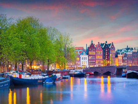 La puesta del sol de primavera colorido en los canales de Amsterdam. Arquitectura holandesa auténtica en la capital y ciudad más poblada de los Países Bajos.