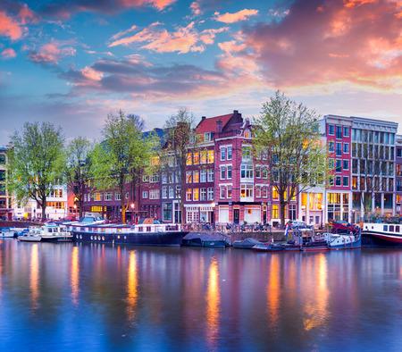 アムステルダムの運河のカラフルな春の夕日。資本とオランダの最も人口の多い都市で本格的なオランダの建築。