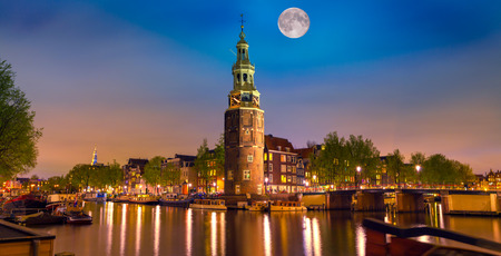amsterdam: Colorful night scene with Montelbaanstoren tower on bank of the canal Oudeschans in Amsterdam, Netherlands.