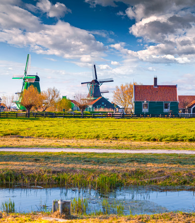 zaan: Authentic Holland architecture on the water channel in Zaanstad village. Zaanse Schans Windmills and famous Netherlands canals, Europe.