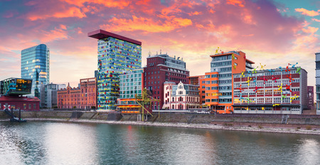 iluminated: Colorful spring sunset on Rhine river in Dusseldorf. Medienhafen in the soft sunset light, Nordrhein-Westfalen, Germany, Europe.