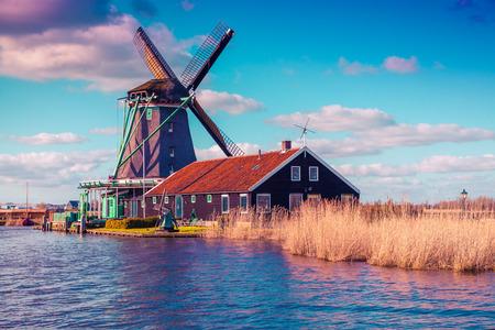Authentic Zaandam mills on the water channel in Zaanstad village. Zaanse Schans Windmills and famous Netherlands canals, Europe. photo