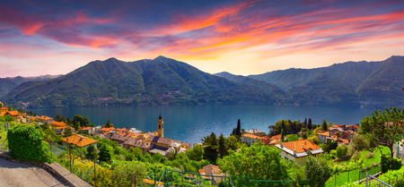 panoramic sky: Colorful summer sunrise on the town of Carate Urio, on Lake Como. Alps, Italy, Lombardi, Europe. Stock Photo