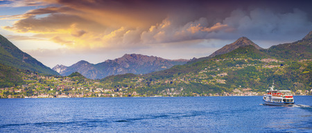 panoramic sky: Travel by boat on the lake Lecco near the Bellagio city at summer sunset. Lombardy, Italy, Europe. Stock Photo
