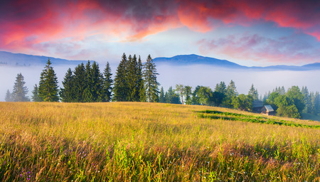 Colorful summer sunrise in Carpathian mountain village.