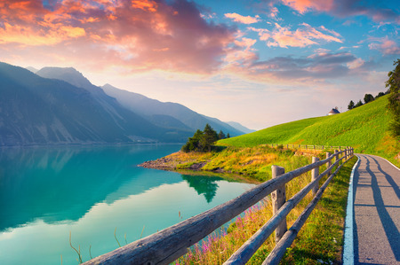 st  valentin: Bicycle path around Resia lake in the Italian Alps. Colorful summer morning on the Reschensee lake. Place is located near the village St. Valentin, Alps, Italy, Europe. Stock Photo