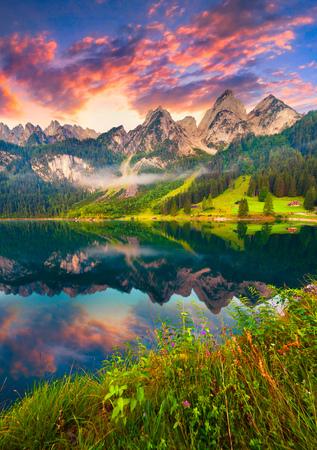 verticales: la salida del sol del verano colorido en el lago Vorderer Gosausee en los Alpes austriacos. Austria, Europa.
