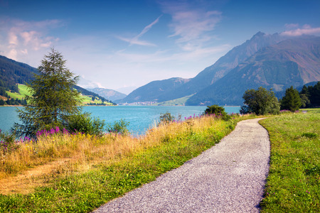 Bicycle path around Resia lake in the Italian Alps. Colorful summer morning on the Reschensee lake. Place is located near the village St. Valentin, Alps, Italy, Europe. Banco de Imagens