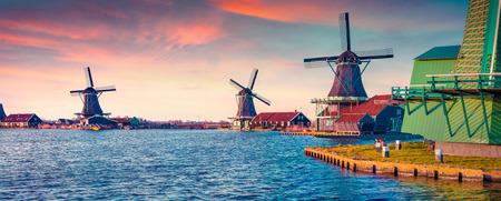 Panorama autentických Zaandam mlýnů na kanál vody v obci Zaanstad. Zaanse Schans větrné mlýny a slavné Nizozemí kanály, Evropa. Instagram tónování.