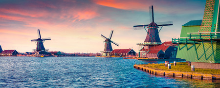 zaanse: Panorama of authentic Zaandam mills on the water channel in Zaanstad village. Zaanse Schans Windmills and famous Netherlands canals, Europe. Instagram toning.