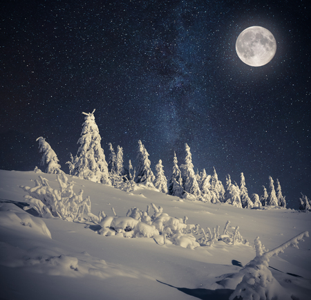 dark landscape: Full moon in night sky in the winter mountains Stock Photo