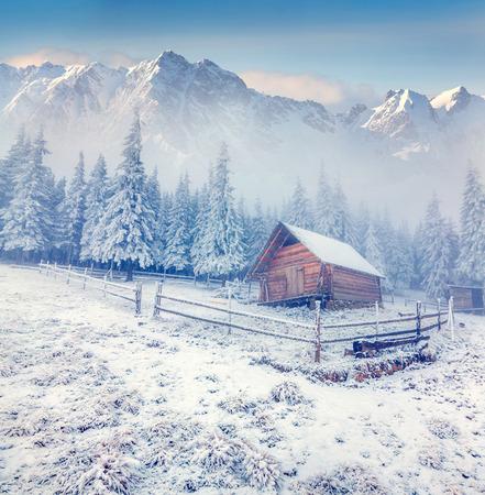 montañas nevadas: Antigua granja en las montañas de invierno niebla. Foto de archivo