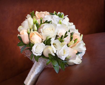 brown leather sofa: Bright roses wedding bouquet on the brown leather sofa. Archivio Fotografico