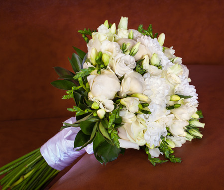 brown leather sofa: Bright flower wedding bouquet on the brown leather sofa. Stock Photo
