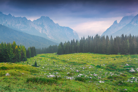 italian landscape: Cresta di Enghe mountain range at foggy summer morning. Dolomites mountains, Italy, Europe.