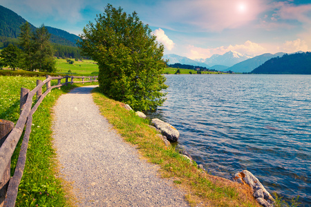 st  valentin: Bicycle path around Muta (Haidersee) lake in the Italian Alps. Colorful summer morning on the Reschensee lake. Place is located near the village St. Valentin, Alps, Italy, Europe. Stock Photo