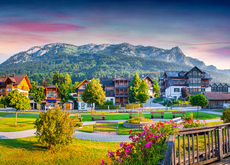 beautiful scenery: Small welcoming village Archkogl in the morning mist. Park on the near Grundlsee lake with beautiful summer flowers. Alps, Austria, Europe. Stock Photo