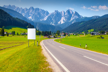 wonderful: Sunny summer scene in the Austrian Alps. Asphalt road in the green mountain valley near alpine village with white billboard for your text. Austria, Europe.