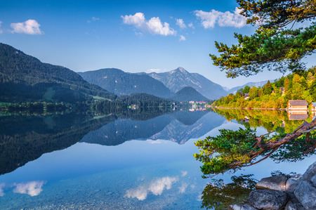 specular: Specular reflection at the water surface of blue mountain in Grundlsee lake. Archkogl village in the morning mist. Alps, Austria, Europe. Stock Photo