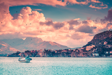 sea cliff: Fishing boat in evening near the Milazzo cape, Mediterranean sea, Sicily, Italy, Europe. Instagram toning.