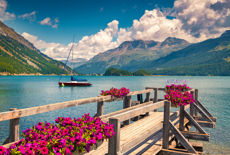 Summer sunny scene on the Silsersee lake with yacht and blooming flowers. Swiss Alps. Segl, Switzerland, Europe. Retro style filtered.