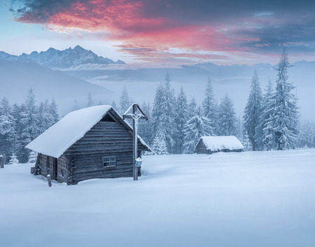 natural background: Old church in the mountains after heavy snowfall. Foggy winter morning. Instagram toning.