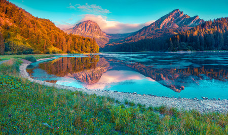 Colorful summer sunrise on the incredibly beautiful Swiss lake Obersee, located near Nafels village. Alps, Switzerland, Europe. Instagram toning.