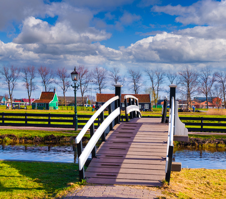 dutch typical: Sunny spring scene in Zaanstad willage in sunny day. Typical Dutch bridge over the canal, Netherlands, Europe.
