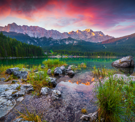 Colorful summer scene on the Eibsee lake in German Alps. Germanys highest mountain Zugspitze 2 962 m, and its mountain ridge in the first rays of sunrise. Germany, Europe. Stock Photo