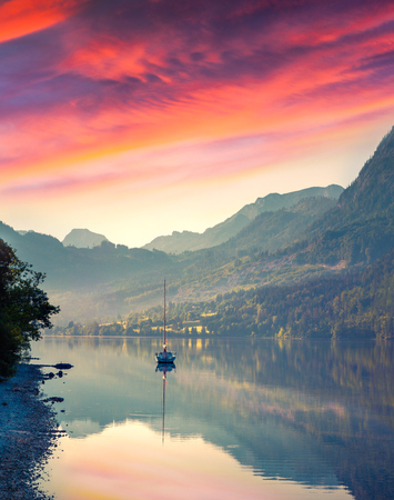 ander: Dramatic summer sunrise on the Grundlsee lake. Small yacht ander a dark red sky near Archkogl village. Alps, Austria, Europe. Stock Photo