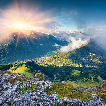 Vista desde el ojo del pájaro de la localidad de Campitello di Fassa en la niebla. Mañana soleada en el Sur del Tirol, Tirol del Sur, Italia, Europa. Foto de archivo - 62216503