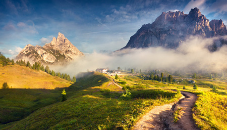 stria: Fantastic summer landscape in Dolomite Alps. Tofane mountain range and Sass de Stria peak in morning mist. View from Falzarego pass.Cortina dAmpezzo location, Province of Belluno, Italy, Europe.