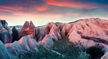 Unreal world of Cappadocia. Sunset in Red Rose valley in April. Cavusin village located, district of Avanos in Nevsehir Province in the Cappadocia region of Turkey, Asia.