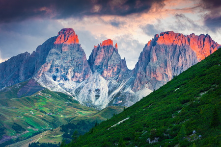 bolzano province: Frst sunlight glowing the tops of spiers of Plattkofel and Langkofel mountain ranges. Sunrise in Dolomite Alps. View from Pordoi pass, Province of Bolzano - South Tyrol, Italy, Europe.