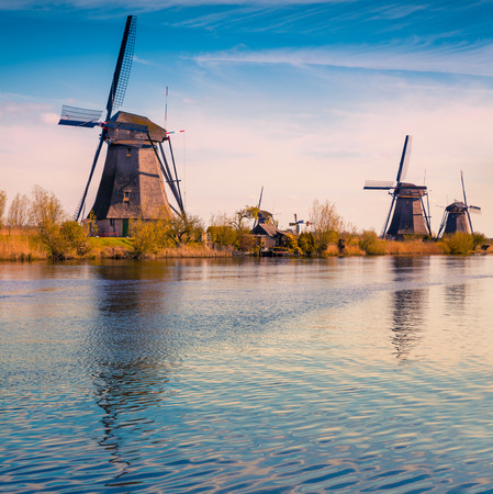 Sunny spring scene in the canal in Netherlands. Dutch windmills at Kinderdijk