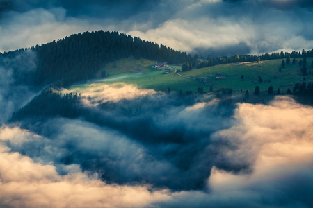 bolzano province: Foggy summer scene in the Dolomite Alps. Ranch at the foot of Furchetta peak. Province of Bolzano, South Tyrol, Italy, Europe. Stock Photo