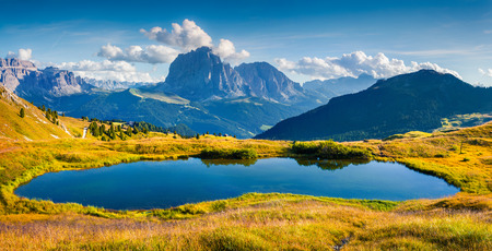 Panorama of Gardena valley with Sassolungo (Langkofel) mountain range. Small lake vnear Troier tourist shelter in Dolomites National Park , South Tyrol. Location Ortisei, S. Cristina and Selva, Italy, Europe.