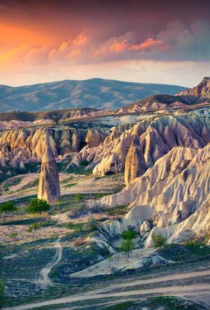 Unreal world of Cappadocia. Sunrise in Red Rose valley in April. Chavushin village located, district of Avanos in Nevsehir Province in the Cappadocia region of Turkey, Asia.