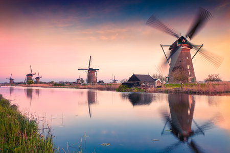 Colorful spring scene in the famoust Kinderdijk canals with windmillas, UNESCO world heritage site. Sunset in Dutch village Kinderdijk, Netherlands, Europe.