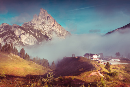 stria: Mt. Sass de Stria in the morning mist. Summer scene in the Falzarego pass. Foggy sunrise in Dolomite Alps, Italy, Europe. Retro style tonned. Stock Photo