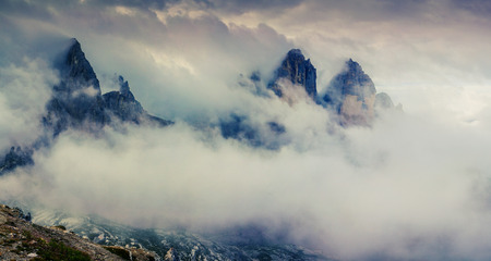 sublime: Tree spires appear in the morning mist in National Park Tre Cime di Lavaredo. Foggy landscape in Dolomite Alps, Location Auronzo, South Tyrol, Italy, Europe.